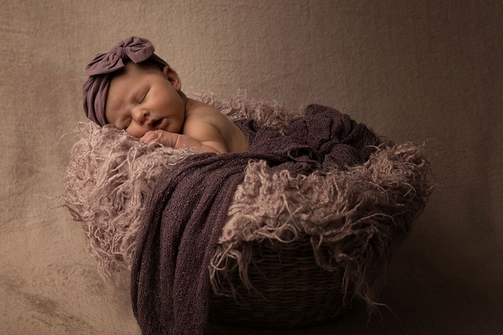 newborn-baby-in-basket-purple-drapes