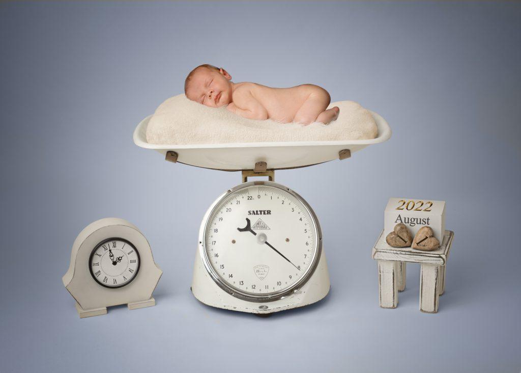 newborn photoshoot baby in scales